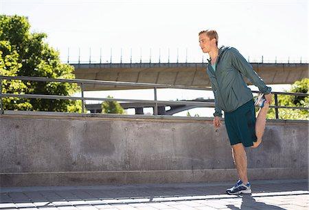 stretching (people exercising) - Full length of man doing stretching exercise on bridge Stock Photo - Premium Royalty-Free, Code: 698-07813008