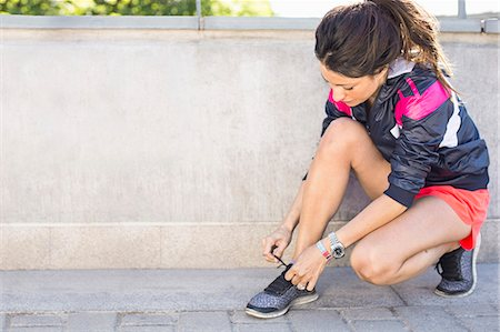 Full length of fit woman tying shoelace before jogging on bridge Stock Photo - Premium Royalty-Free, Code: 698-07813009