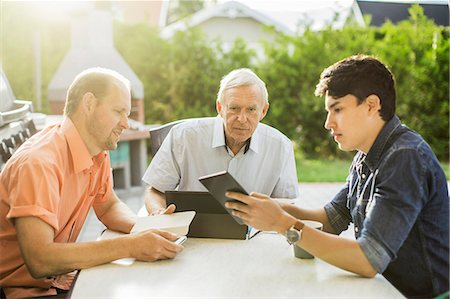 Three generation males using technologies at table in yard Stock Photo - Premium Royalty-Free, Code: 698-07813003