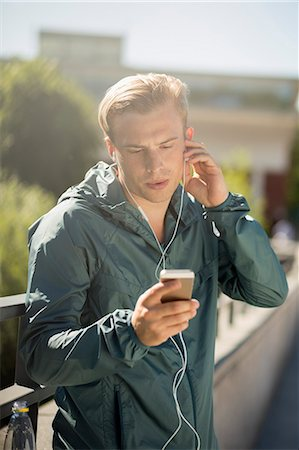 physical fitness - Fit man listening music through smart phone on bridge Stock Photo - Premium Royalty-Free, Code: 698-07813015