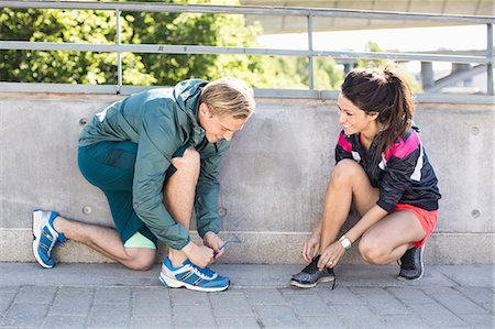 physical fitness - Smiling fit couple tying shoelaces before jogging on bridge Stock Photo - Premium Royalty-Free, Code: 698-07813010