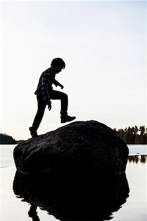 silhouettes - Full length of boy moving up rock against clear sky Stock Photo - Premium Royalty-Free, Code: 698-07813045