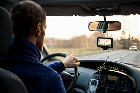 Rear view of man driving car while using GPS Stock Photo - Premium Royalty-Free, Code: 698-07813046