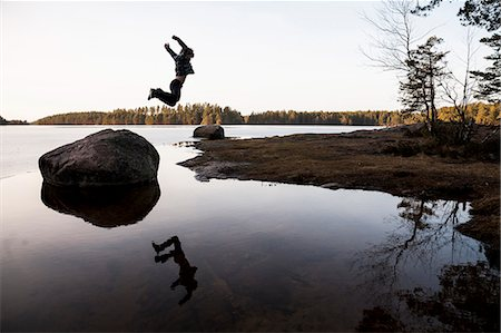 Full length of boy jumping off stone over water Stock Photo - Premium Royalty-Free, Code: 698-07813043