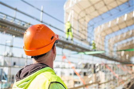 Rear view of worker looking at colleagues working at construction site Stock Photo - Premium Royalty-Free, Code: 698-07813089