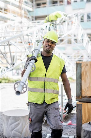 Construction worker looking away while carrying metal rod at site Stock Photo - Premium Royalty-Free, Code: 698-07813107