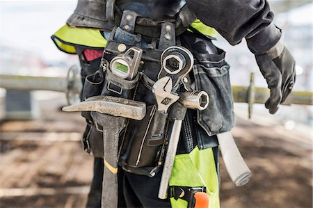 Midsection of construction worker wearing tool belt at site Stock Photo - Premium Royalty-Free, Code: 698-07813100