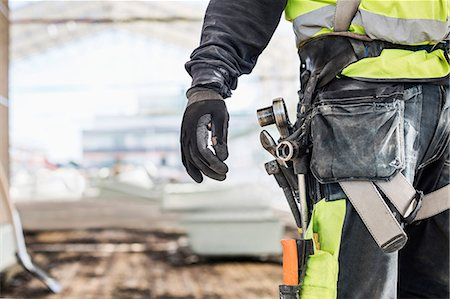 Midsection of worker wearing tool belt at construction site Stock Photo - Premium Royalty-Free, Code: 698-07813101