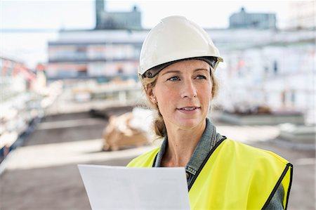 female - Female architect looking away while working at construction site Stock Photo - Premium Royalty-Free, Code: 698-07813102