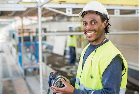 Portrait of happy worker at construction site Stock Photo - Premium Royalty-Free, Code: 698-07813114