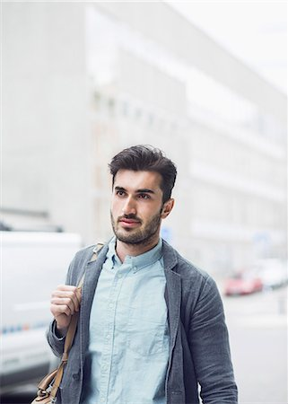 Young businessman looking away while walking on city street Stock Photo - Premium Royalty-Free, Code: 698-07813119