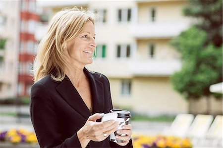 Happy businesswoman looking away while holding smart phone and disposable coffee cup outdoors Stock Photo - Premium Royalty-Free, Code: 698-07813126