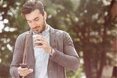 Young businessman having coffee while using smart phone outdoors Stock Photo - Premium Royalty-Free, Code: 698-07813122