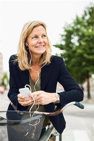Smiling businesswoman listening music through smart phone while leaning on bicycle outdoors Stock Photo - Premium Royalty-Free, Code: 698-07813144