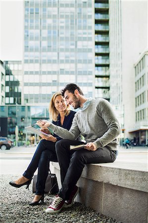 Business people discussing over digital tablet while sitting on seat in city Stock Photo - Premium Royalty-Free, Code: 698-07813141