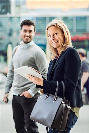 Portrait of businesswoman using digital tablet on city street with colleague in background Stock Photo - Premium Royalty-Free, Code: 698-07813143