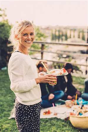 Side view portrait of happy woman holding breakfast at rooftop party Stock Photo - Premium Royalty-Free, Code: 698-07813157