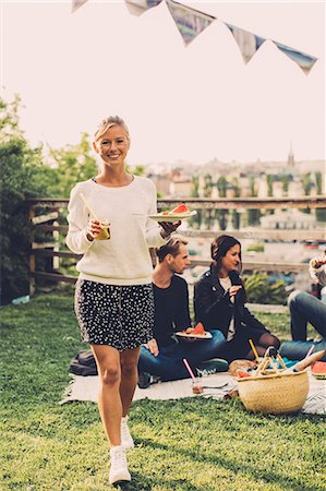 Portrait of happy woman with breakfast walking at rooftop party Stock Photo - Premium Royalty-Free, Code: 698-07813158
