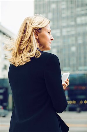 Rear view of businesswoman holding smart phone on city street Stock Photo - Premium Royalty-Free, Code: 698-07813150