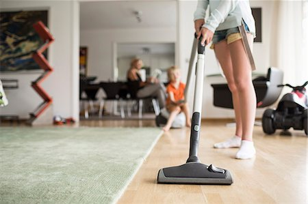 Low section of girl cleaning floor with vacuum cleaner at home Stock Photo - Premium Royalty-Free, Code: 698-07813174