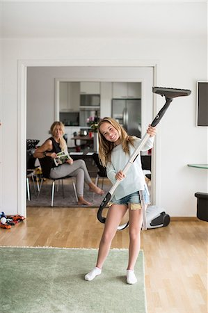 Full length portrait of playful girl holding vacuum cleaner at home with mother sitting in background Stock Photo - Premium Royalty-Free, Code: 698-07813175