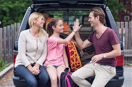 Smiling woman looking at father and daughter giving high-five in car trunk Stock Photo - Premium Royalty-Free, Code: 698-07813171