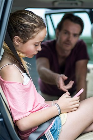 Daughter ignoring father while using mobile phone in car Stock Photo - Premium Royalty-Free, Code: 698-07813173