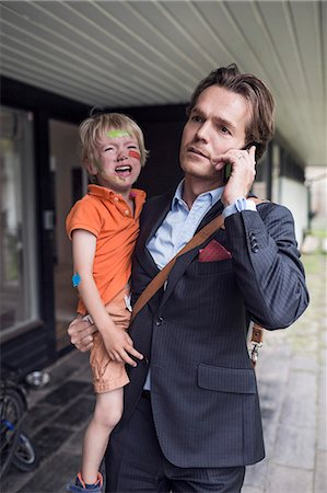people - Businessman using mobile phone while carrying crying son outside house Stock Photo - Premium Royalty-Free, Code: 698-07813186