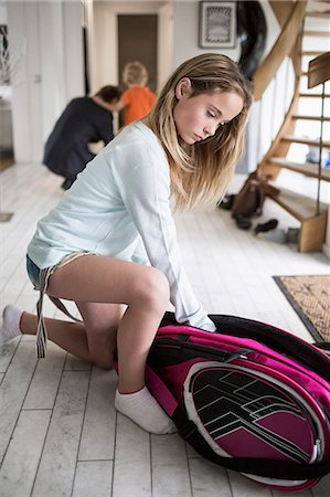Girl packing badminton bag at home with family in background Stock Photo - Premium Royalty-Free, Code: 698-07813188