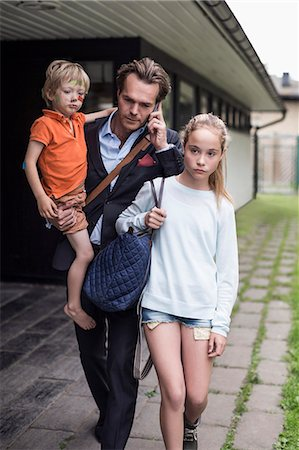 Businessman using mobile phone while walking with children at yard Stock Photo - Premium Royalty-Free, Code: 698-07813183
