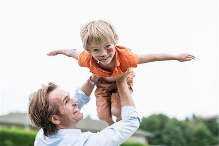 father with two sons not girls - Playful father lifting injured son against clear sky Stock Photo - Premium Royalty-Free, Code: 698-07813194