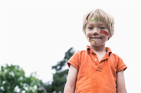 Portrait of injured boy standing against clear sky Stock Photo - Premium Royalty-Free, Code: 698-07813196