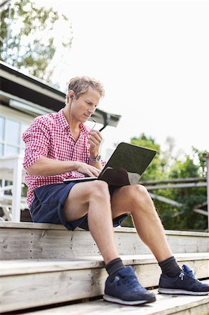 Man using hands-free device and laptop while sitting on porch against clear sky Stock Photo - Premium Royalty-Free, Code: 698-07944447
