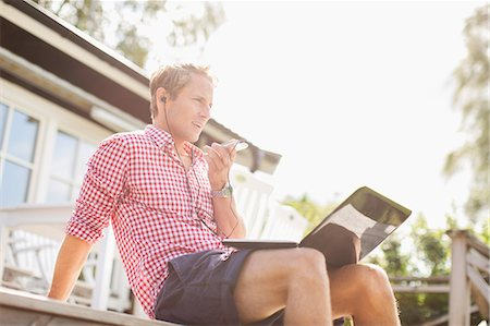 Man talking through hands-free device on porch against clear sky Stock Photo - Premium Royalty-Free, Code: 698-07944449
