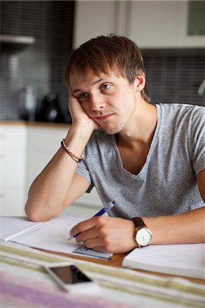 studying (all students) - Bored man looking away while studying at table in house Stock Photo - Premium Royalty-Free, Code: 698-07944485