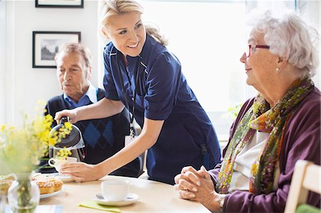 Happy female caretaker serving coffee to senior people at nursing home Stock Photo - Premium Royalty-Free, Code: 698-07944489