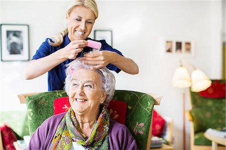 Happy female caretaker putting curlers to senior woman's hair at nursing home Stock Photo - Premium Royalty-Free, Code: 698-07944496