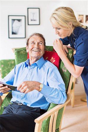 Happy senior man looking female caretaker while using digital tablet in nursing home Stock Photo - Premium Royalty-Free, Code: 698-07944499
