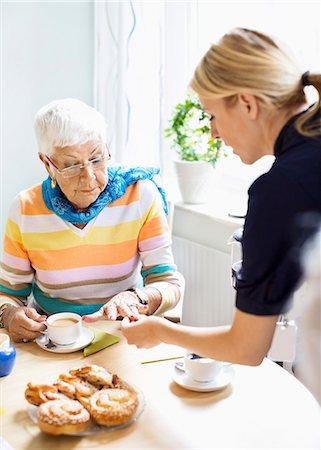 Female caretaker examining senior woman's finger at breakfast table in nursing home Stock Photo - Premium Royalty-Free, Code: 698-07944490