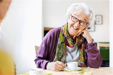 Happy senior woman looking at friend while having coffee at breakfast table in nursing home Stock Photo - Premium Royalty-Free, Code: 698-07944491