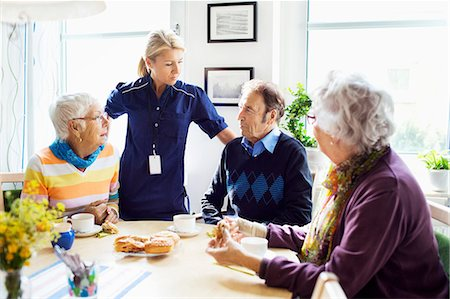 Female caretaker with senior people discussing at breakfast table in nursing home Stock Photo - Premium Royalty-Free, Code: 698-07944492