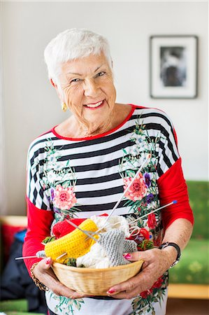 Portrait of happy senior woman holding knitting basket at nursing home Stock Photo - Premium Royalty-Free, Code: 698-07944508