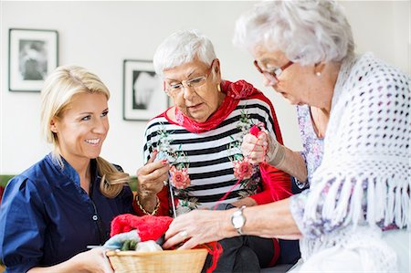 senior women - Happy female caretaker looking at senior women choosing wool for knitting at nursing home Stock Photo - Premium Royalty-Free, Code: 698-07944502