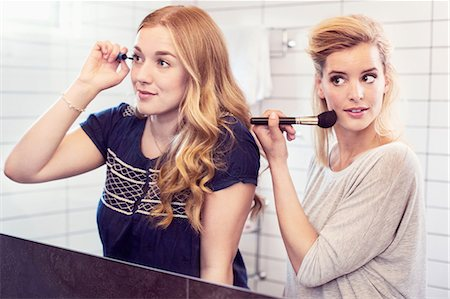 Young sisters applying makeup in mirror Stock Photo - Premium Royalty-Free, Code: 698-07944519
