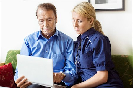 Female caretaker and senior man using laptop at nursing home Stock Photo - Premium Royalty-Free, Code: 698-07944510