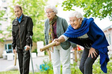 Happy senior people playing kubb game at park Stock Photo - Premium Royalty-Free, Code: 698-07944511