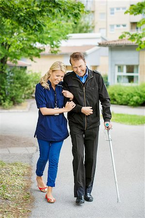 Full length of happy female caretaker walking with disabled senior man on street Stock Photo - Premium Royalty-Free, Code: 698-07944512