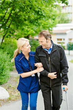 Happy female caretaker walking with disabled senior man on street Stock Photo - Premium Royalty-Free, Code: 698-07944513