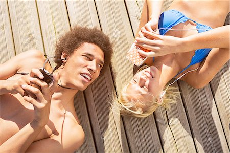 Man looking at woman using smartphone while lying on boardwalk Stock Photo - Premium Royalty-Free, Code: 698-07944525