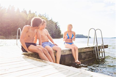 Friends enjoying while sitting on boardwalk at lake Stock Photo - Premium Royalty-Free, Code: 698-07944529